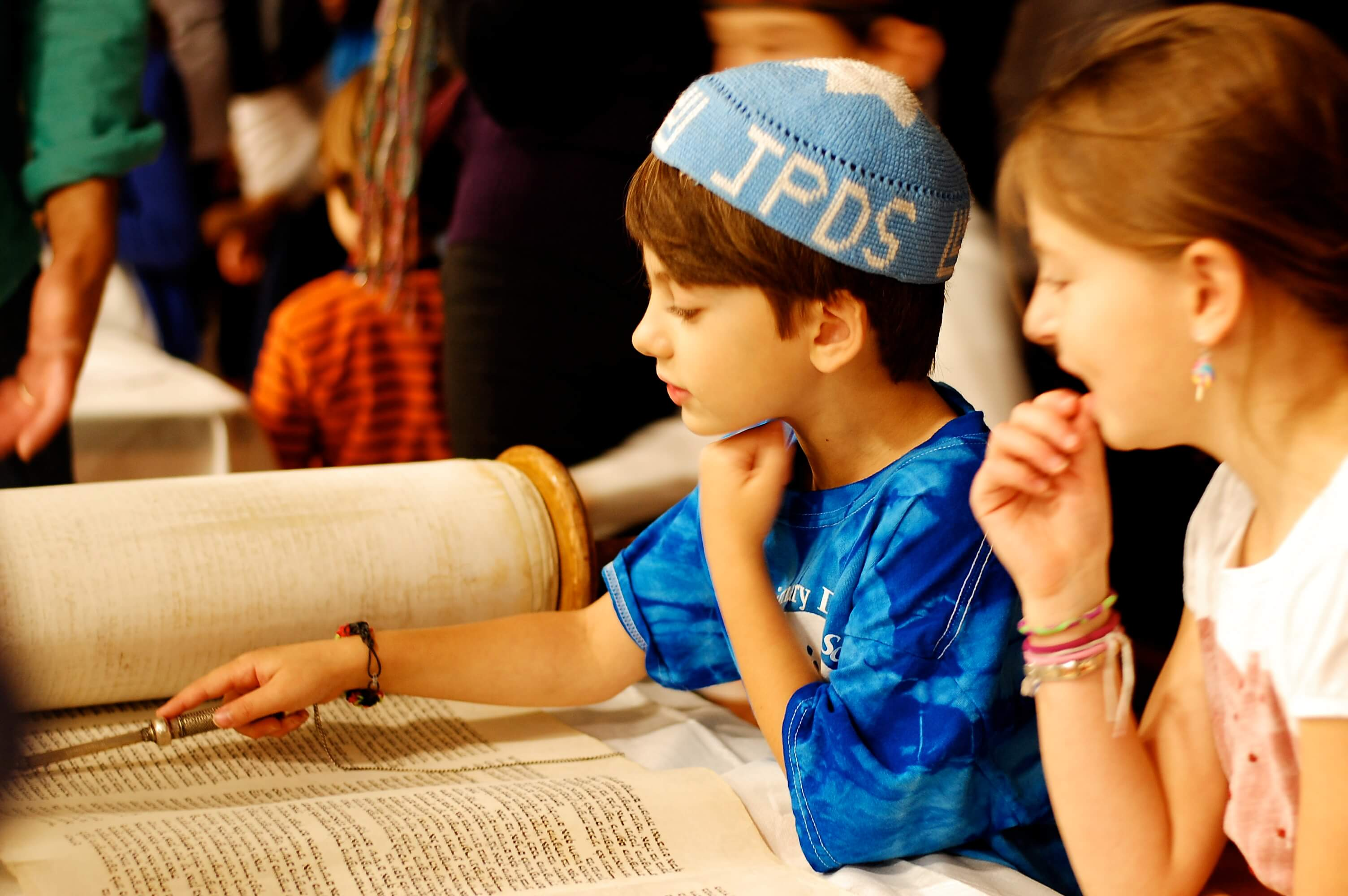 Students learn about different types of Torah scrolls at a school event.