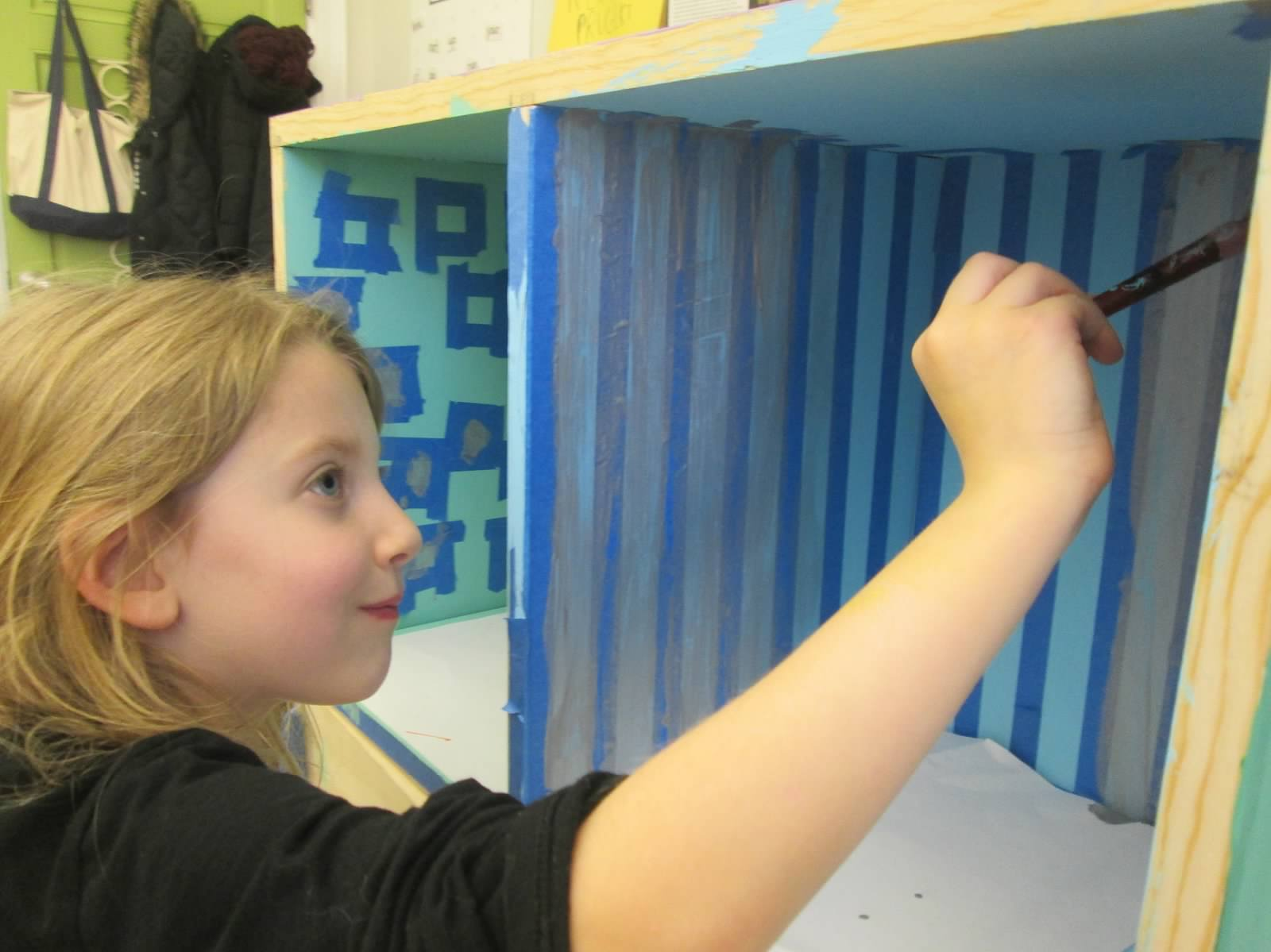 A student paints one of the new library bookshelves with colors decided by a class vote.