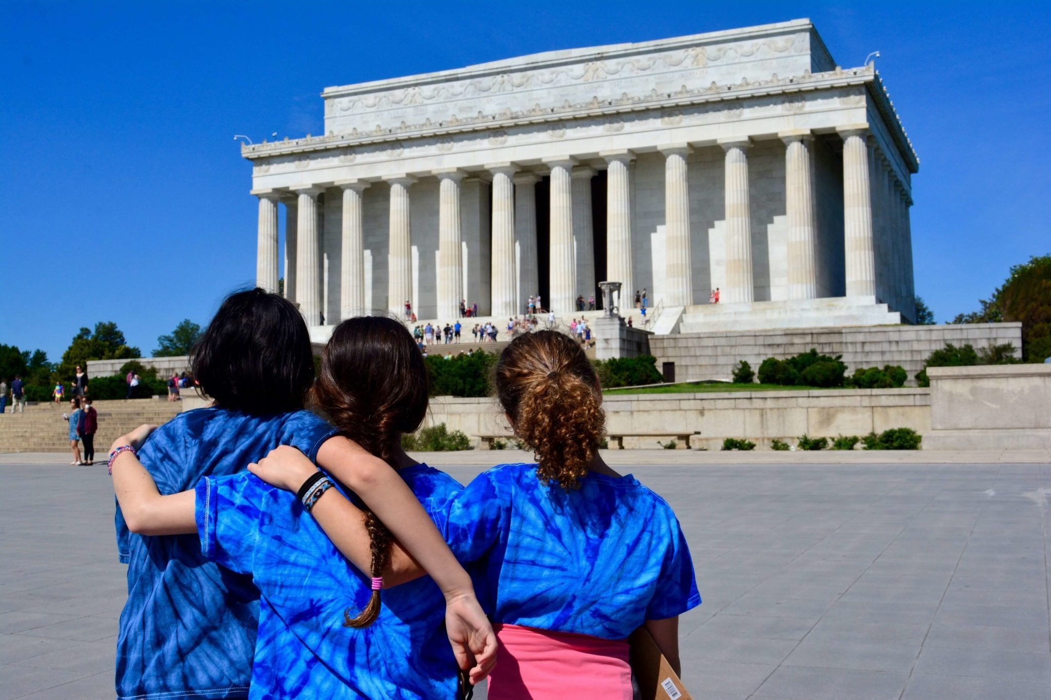 Three girls in JPDS-NC shirts stand arm in arm at the Lincoln Memorial.