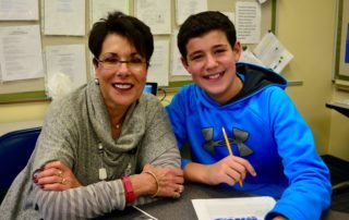 A student and his grandmother smile together on Share the Nachas Day.