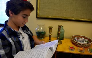 A student reads from his chumash (copy of the Torah).