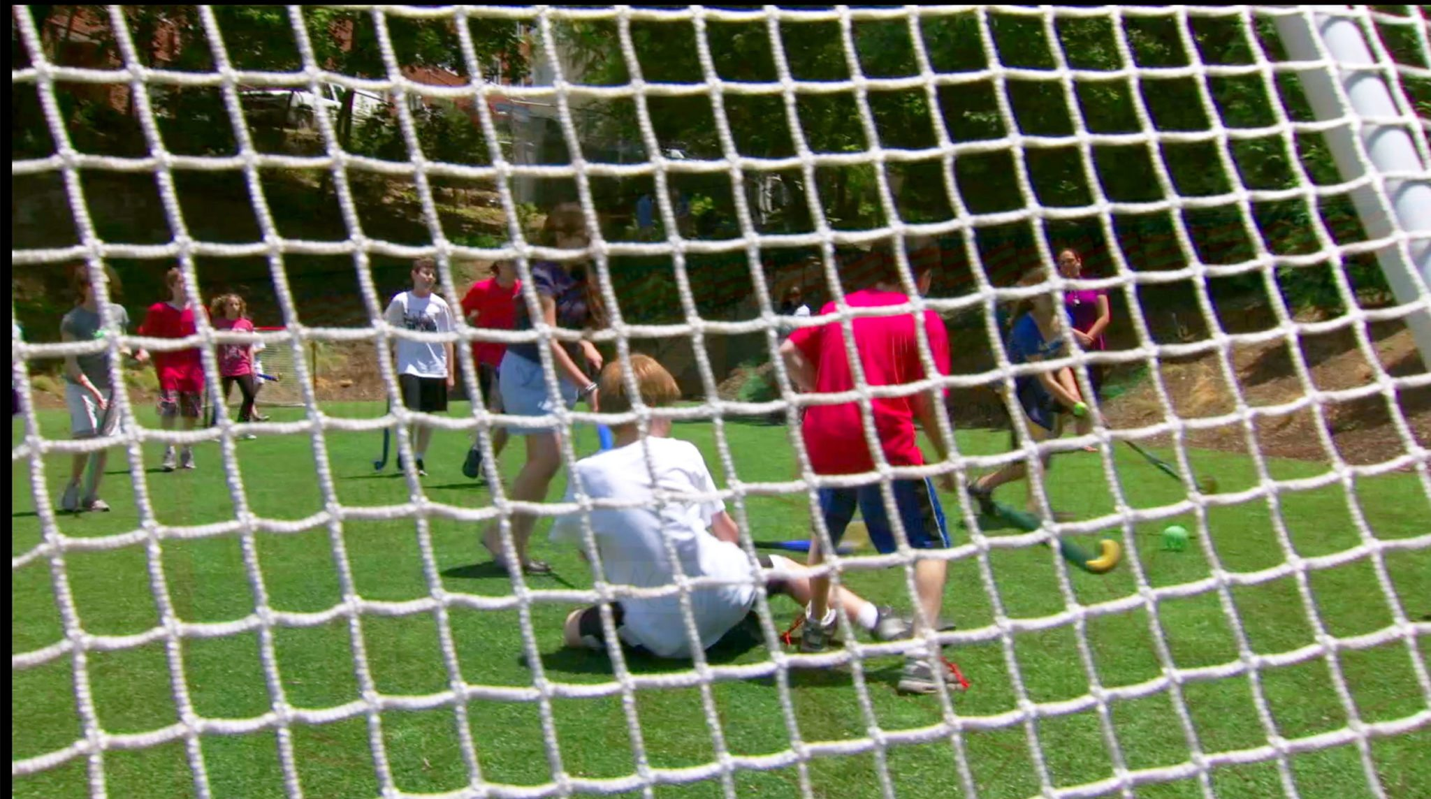 Students play field hockey together on the chatzer (field).
