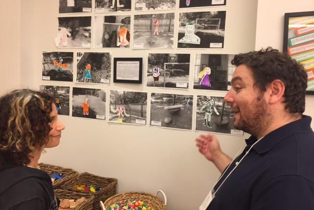 Kindergarten teacher Vas Pournaras talks about displayed student work at the DCREA meeting.