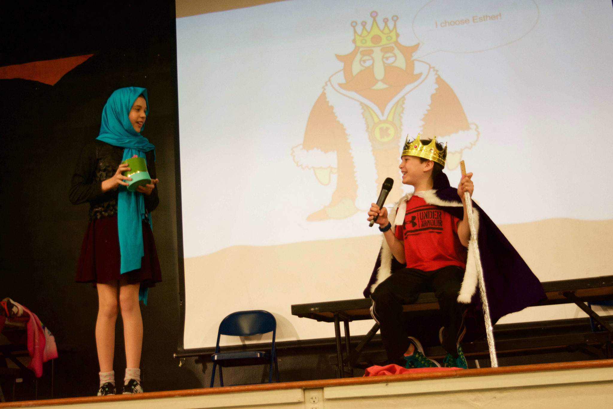 King Achashverosh and Queen Esther on stage for the Sixth Grade Purim Spiel.