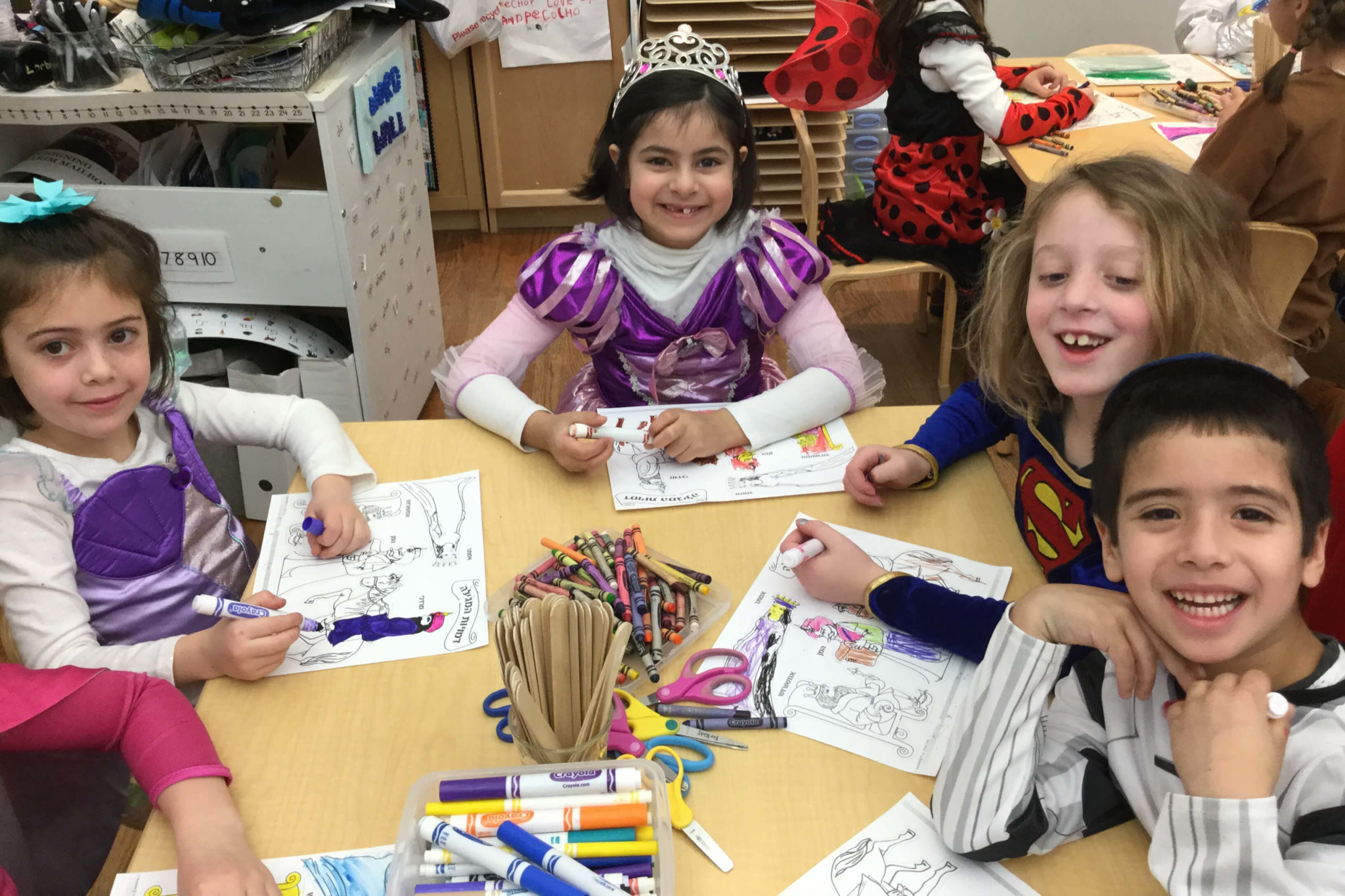 A princess and Supergirl work on Purim-themed arts and crafts at the South Campus Purim Carnival.