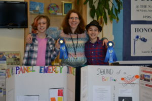 From left to right, STEM Fair winner Yael N., Science Specialist Elana Cohen, and STEM Fair Winner Gabriel B. pose with the students' project boards and blue ribbons.